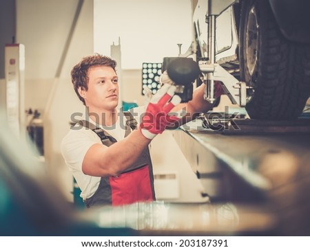 Serviceman checking wheel alignment  in a car workshop  - stock photo
