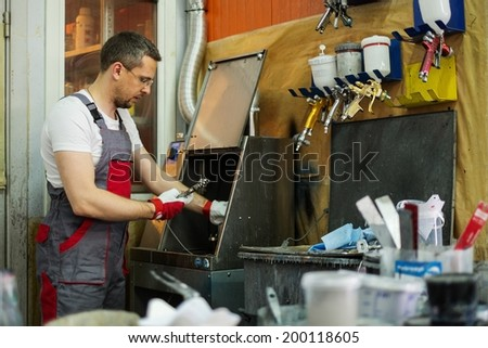 Serviceman cleaning airbrush gun in a car body workshop - stock photo
