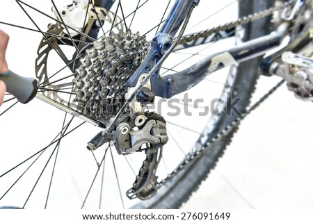 Serviceman hand repair bicycle whee with screwdriver. Bicycle gears and rear derailleur repair. A bicycle repairing. Mountain bike is repaired - stock photo