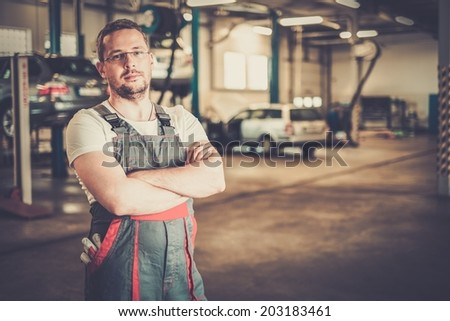Serviceman in a car workshop - stock photo