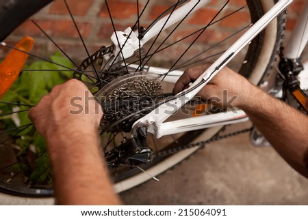 Serviceman repairing a bicycle tire with a tools - stock photo