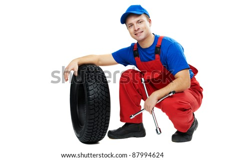 serviceman repairman automobile mechanic with car tire and spanner wrench isolated - stock photo