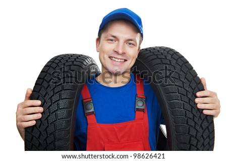 serviceman repairman automobile mechanic with two car tyres isolated - stock photo