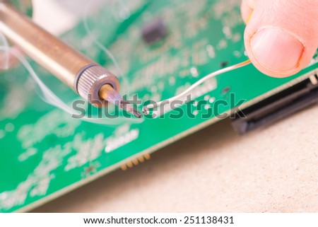 Serviceman soldering PCB with soldering iron in the service workshop - stock photo