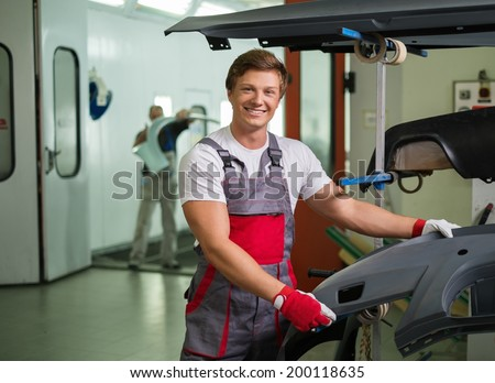 Serviceman with car bodykit ready for painting in a workshop - stock photo