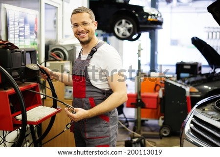 Serviceman with co/hc diagnostic tool in a car workshop - stock photo