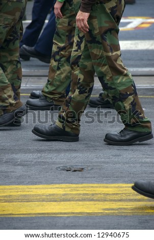 Servicemen and women march in formation - stock photo