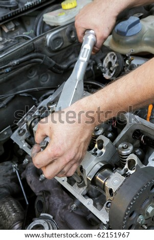 Servicing of modern car engine hands with tool