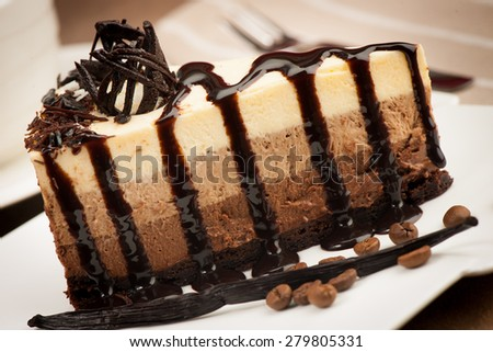 Serving a chocolate cake on a plate with vanila stroke and coffee beans, applying a syrup - stock photo