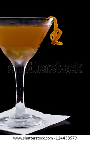serving a manhattan cocktail garnished with an orange twist on a dark bar setting - stock photo