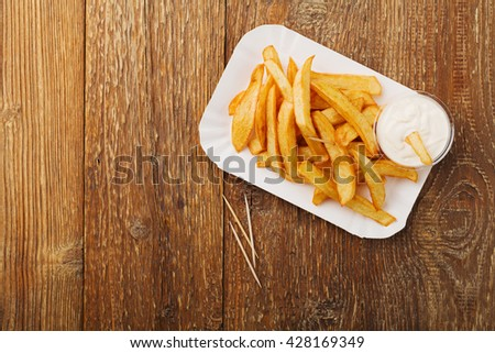 Serving Belgian fries served on a paper tray, with or without a dip. On a wooden table.