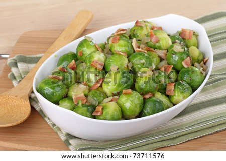 Serving bowl of brussels sprouts with bacon pieces on top - stock photo