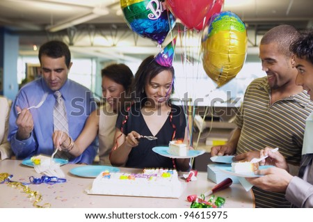 Serving cake at office birthday party - stock photo