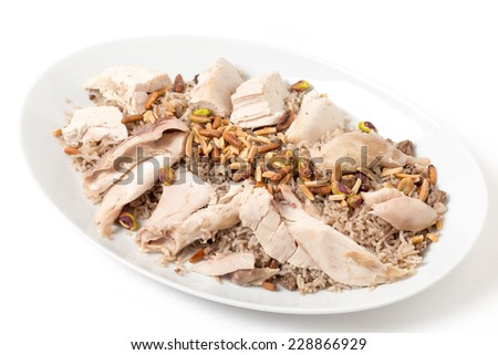 Serving dish of Lebanese chicken and spiced rice with meat and roast nuts, a speciality for celebrations in the Levant - stock photo