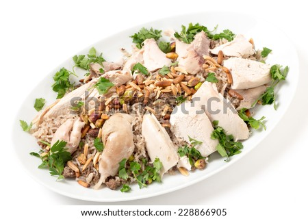 Serving dish of Lebanese chicken and spiced rice with meat,  roast nuts and a parsley garnish, a speciality for celebrations in the Levant - stock photo