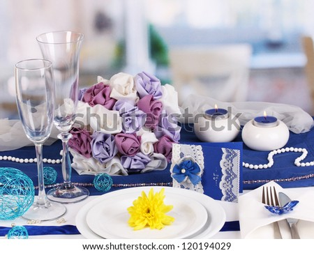 Serving fabulous wedding table in purple and blue color of the restaurant background - stock photo