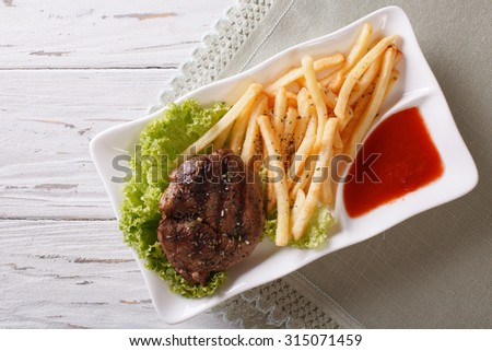 Serving grilled beefsteak with french fries and sauce on a plate. horizontal view from above