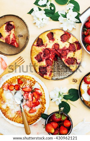 Serving homemade strawberry cake or pie on wooden rustic table. Tart with fresh strawberry on wooden background. Strawberry tart  with icing sugar and whole fruits onwith cooking utensils. Rustic styl