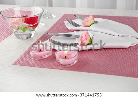 Serving in a napkin with spoon and fork for two person on pink background - stock photo