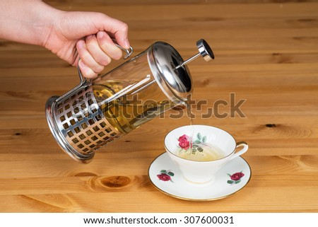 Serving linden tea from french press to a mug - stock photo
