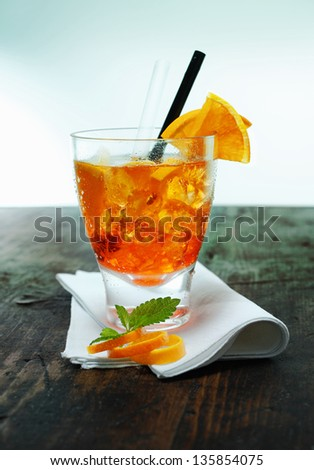 Serving of aperol spritz cocktail with ice garnished with mint leaves and orange rind on a folded napkin on an old wooden counter in a bar or club