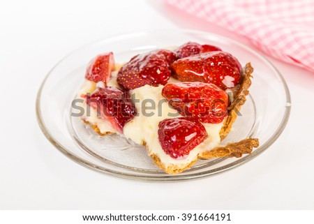 Serving of Apple-glazed Strawberry Cheesecake on clear glass dish with pink gingham napkin on white background.