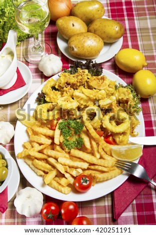 Serving of breaded and deep-fried calamari and fries on a white plate served on a table with fresh vegetables, lemon and a glass of white wine. - stock photo