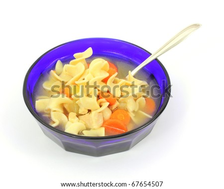 Serving of chicken soup with pasta and carrots in a colorful blue bowl with a spoon on a white background. - stock photo