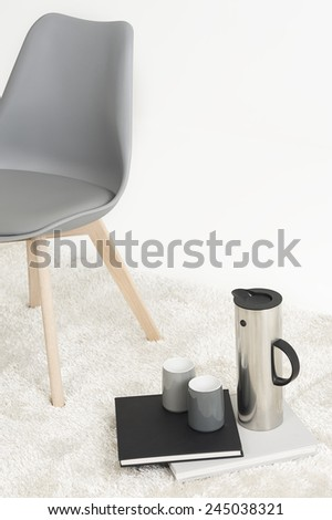 Serving of coffee alongside a modern molded chair with two empty mugs and an elegant tall flask resting on two hardcover books on a white carpet, with copyspace - stock photo