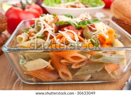 serving of colored penne pasta with tomato sauce, cheese and basil - stock photo