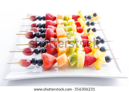 Serving of colorful fresh tropical fruit kebabs on a modern rectangular white plate viewed low angle with receding perspective on white - stock photo
