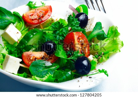 Serving of delicious Greek salad with feta cheese, olives, herbs, tomato and lettuce in an individual dish as an accompaniment to a meal