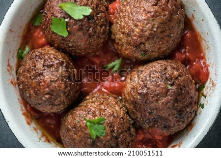 Serving of delicious seasoned meatballs in tomato sauce garnished with fresh herbs, overhead view in a saucepan - stock photo