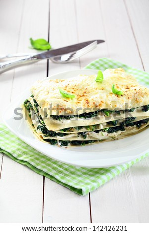 Serving of fresh baked vegetarian spinach lasagna on a plate over a napkin and an old white wooden table - stock photo