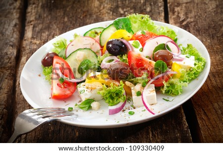 Serving of fresh healthy mixed salad with leafy greens, radish, tomato, olives and cheese served on a rustic wooden table - stock photo