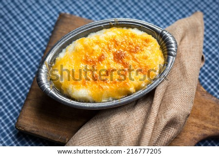 Serving of freshly baked cheese grits in small pewter casserole dish. - stock photo