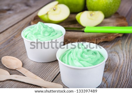 Serving of frozen homemade creamy ice yoghurt  with fresh green apples and wooden spoon - stock photo