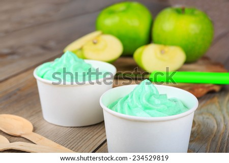 Serving of frozen homemade creamy ice yoghurt  with fresh green apples and wooden spoon. Green healthy bio organic and vegan dessert. - stock photo