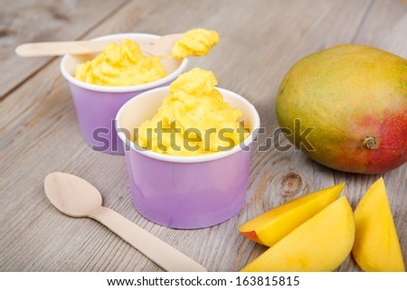 Serving of frozen homemade creamy ice yoghurt  with fresh mango and wooden spoon - stock photo