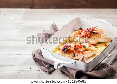 Serving of golden roasted chicken breasts in a metal oven dish topped with diced red pepper,onion and herbs and served on a picnic table with copyspace - stock photo