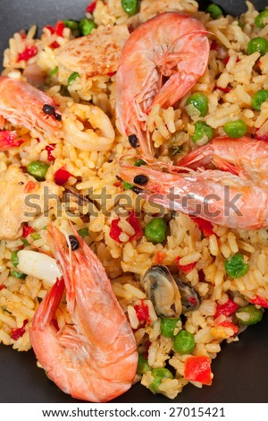 serving of spanish paella on dark background - stock photo