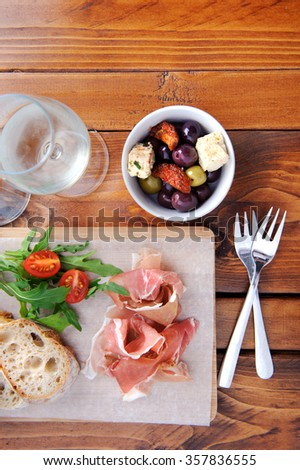 Serving of traditionally italian antipasto, prosciutto with bread and olives with wine  - stock photo