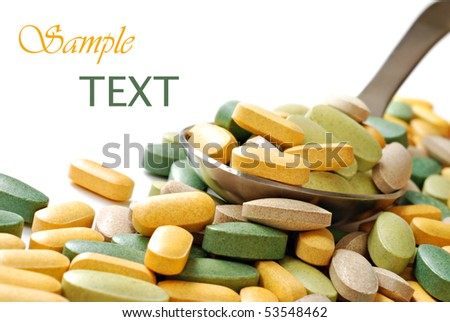 Serving spoon overflowing with vitamins on white background with copy space.  Macro with shallow dof. - stock photo