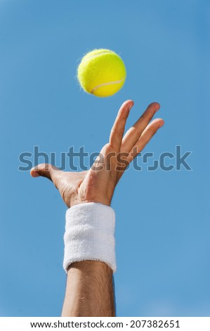 Serving tennis ball. Close-up of male hand in wristband throwing tennis ball against blue sky - stock photo