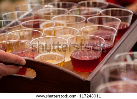 Serving tray with juice cups being carried - stock photo