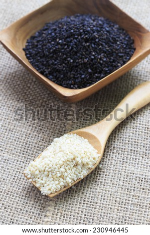 Sesame and black sesame seeds in a wooden spoon. - stock photo
