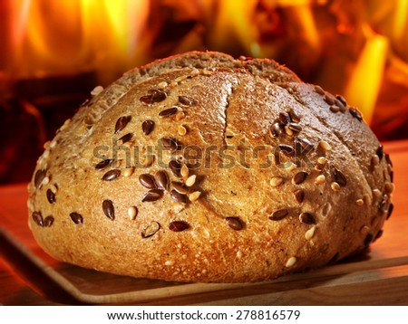 Sesame bun on wooden board on background of fire.