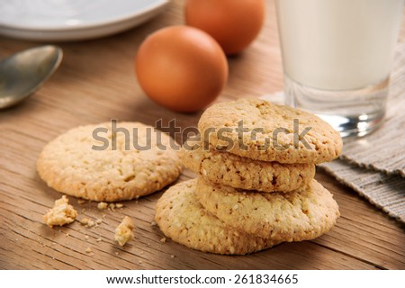 sesame cookies with a glass of milk on wooden table - stock photo