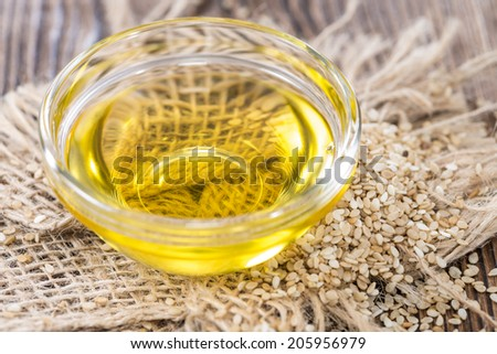 Sesame Oil with some Sesame Seeds on dark wooden table (close-up shot) - stock photo
