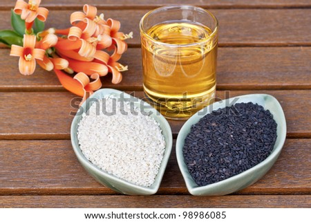 Sesame seed and sesame oil on a teak table - stock photo